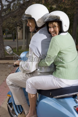 senior couple riding on blue motor