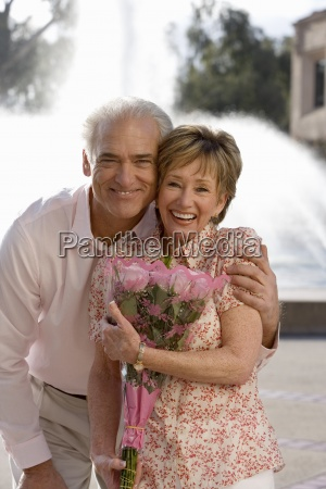 senior couple standing near water fountain