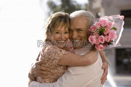 senior couple embracing near water fountain