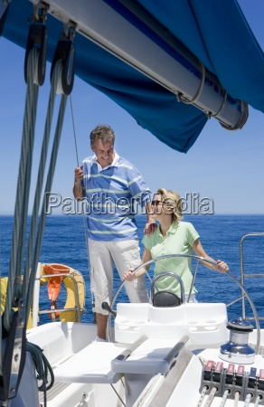 couple standing at helm of sailing