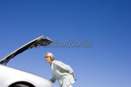 senior woman experiencing car trouble looking