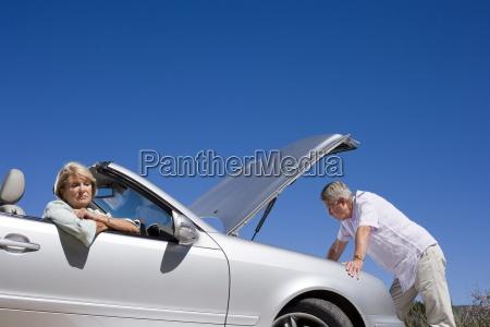 senior couple experiencing car trouble sombre