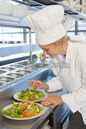 confident smiling chef preparing salad plates