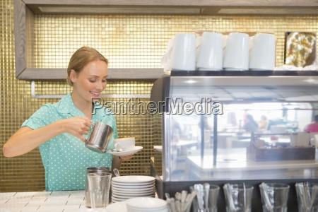 laechelnde kellnerin giessen tasse kaffee in