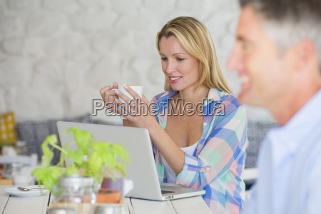 woman with cup of coffee using