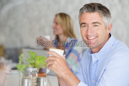 smiling man drinking cup of coffee