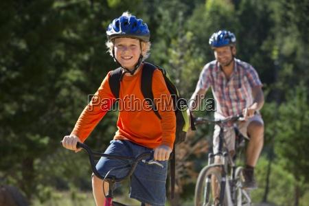vater und sohn reiten mountainbikes im