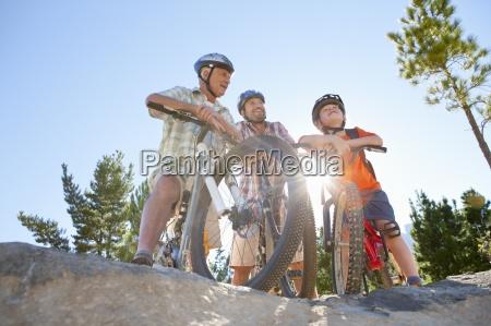 drei generationen von maennern reiten mountainbikes