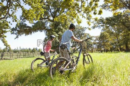 family pushing mountain bikes in rural