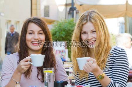 zwei junge frauen im strassencafe