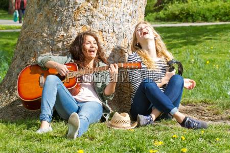zwei freundinnen beim musik machen im