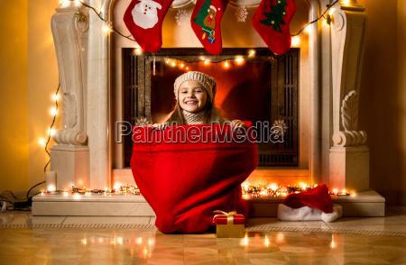 girl sitting in big red sack