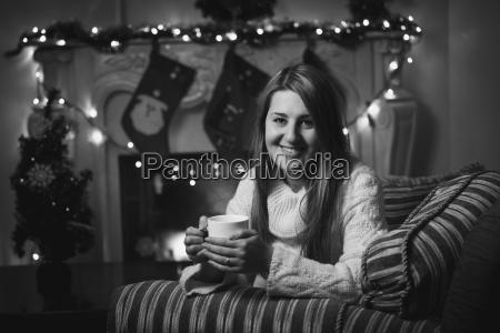 monochrome portrait of smiling woman drinking