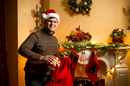 man holding red santa bag with