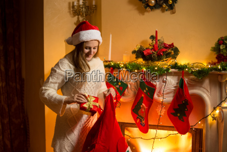 young mother putting christmas gifts in