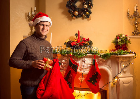 smiling man putting presents in christmas