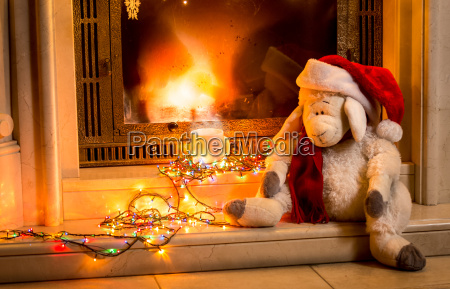 toy sheep sitting next fireplace at