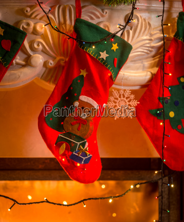 red christmas stockings hanging on fireplace