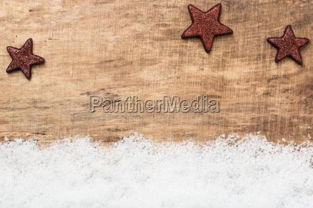 weihnachtssterne vor rustikalem holz mit schnee