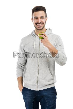 man tasting a green fresh apple