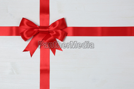 geschenk band mit schleife auf holzbrett