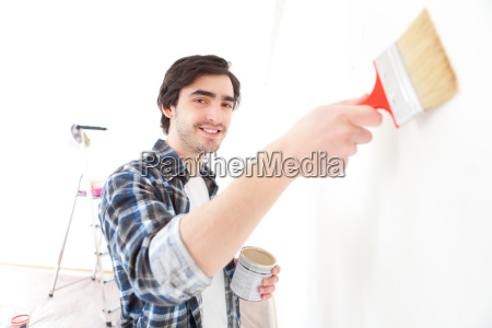 attractive young man painting a wall
