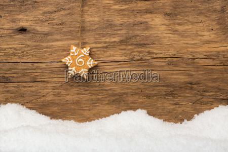 haengender lebkuchen mit schnee auf holz
