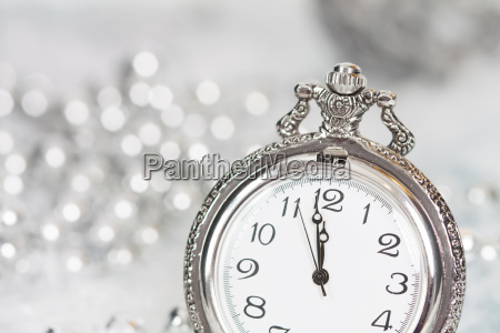 old silver clock close to midnight