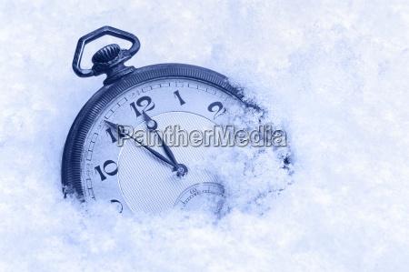 pocket watch in snow happy new