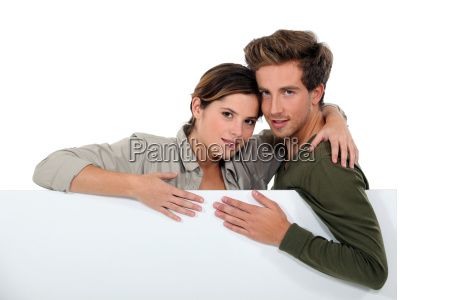 couple stood with blank poster