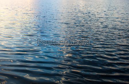 wasseroberflaeche mit wellen und sonnenstrahlen reflexionen