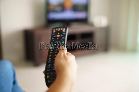 frau sitzt mit remote tv wechsel