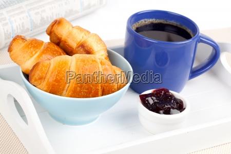 fruehstueck mit croissant marmelade und kaffee