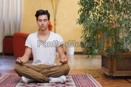 junger mann meditiert auf dem boden