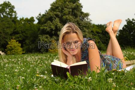 frau entspannt beim lesen im park
