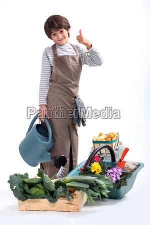 ein kleiner junge in gaertner gekleidet