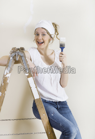 woman with brush on ladder