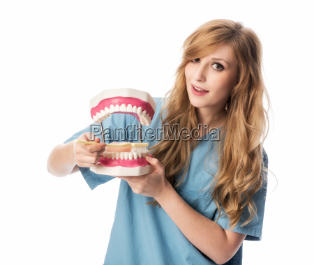 woman with tooth model and toothbrush