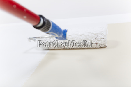 paint roller with white paint on