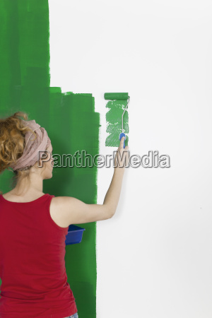 woman painting wall green