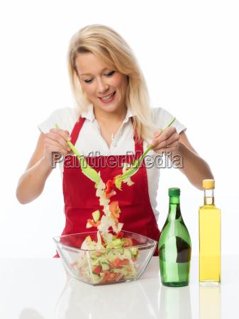 hausfrau ruehrt mit einem salatbesteck einen