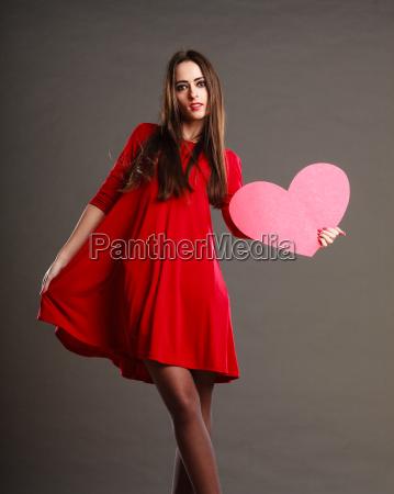 frau im roten kleid haelt herz