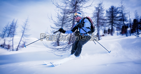man skiing in powder snow in