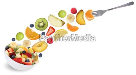 flying fruit salad with fork fruits