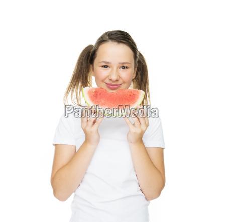 laechelnde junge maedchen essen eine scheibe