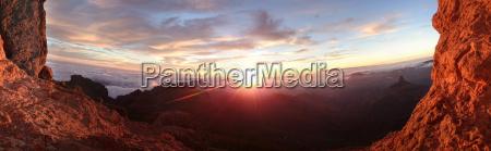 feuriger sonnenaufgang ueber einer berglandschaft