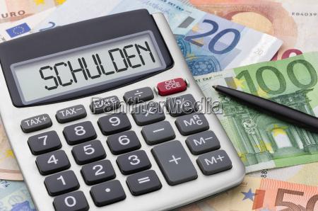 taschenrechner mit geldscheinen schulden