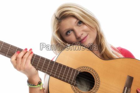 junge blonde frau spielt gitarre und