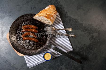 rostbratwuerste mit sauerkraut in einer pfanne
