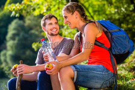 paar bei wandern im sommer trinkt
